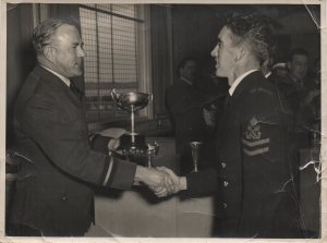 1955-07-27-je-nolan-receiving-nz-inter-services-football-trophy-from-an-air-cdre-rnzaf-possibly-devonport-naval-base-sports-fields-clubhouse-front